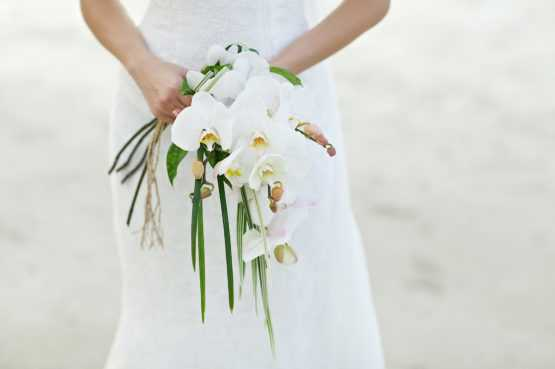 A bride on a beach holding a large bouquet of flowers