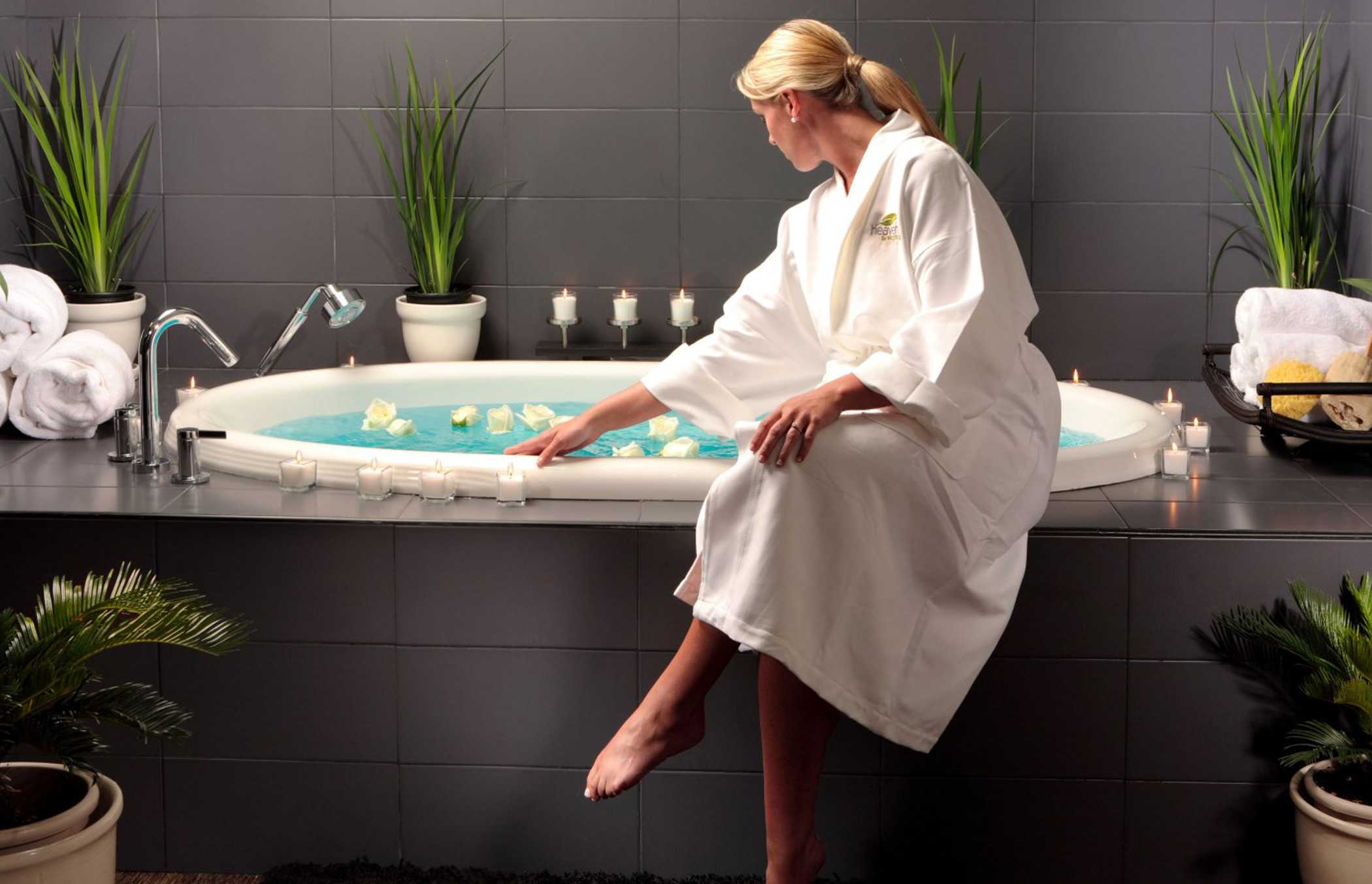 A woman in a robe sitting on the edge of a candlelit spa jacuzzi tub