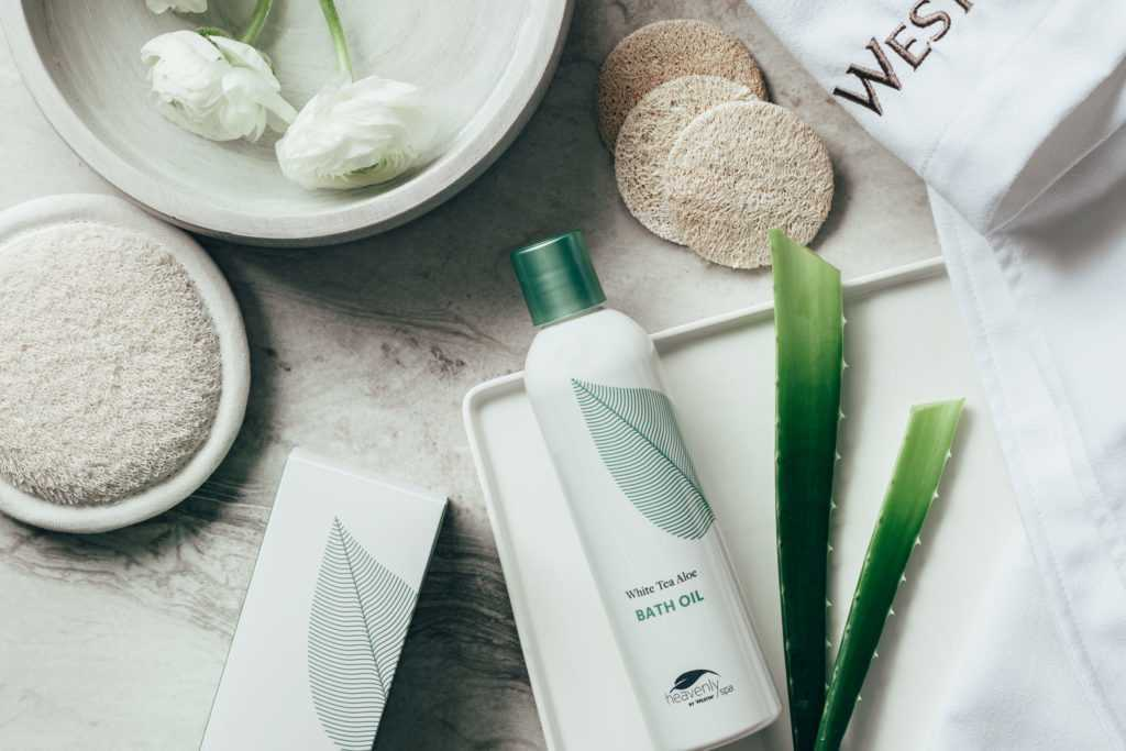 Clean white spa products laid out beside fresh aloe and flowers
