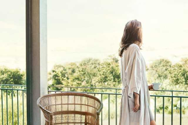 A woman in a robe looking over her balcony to view the scenery