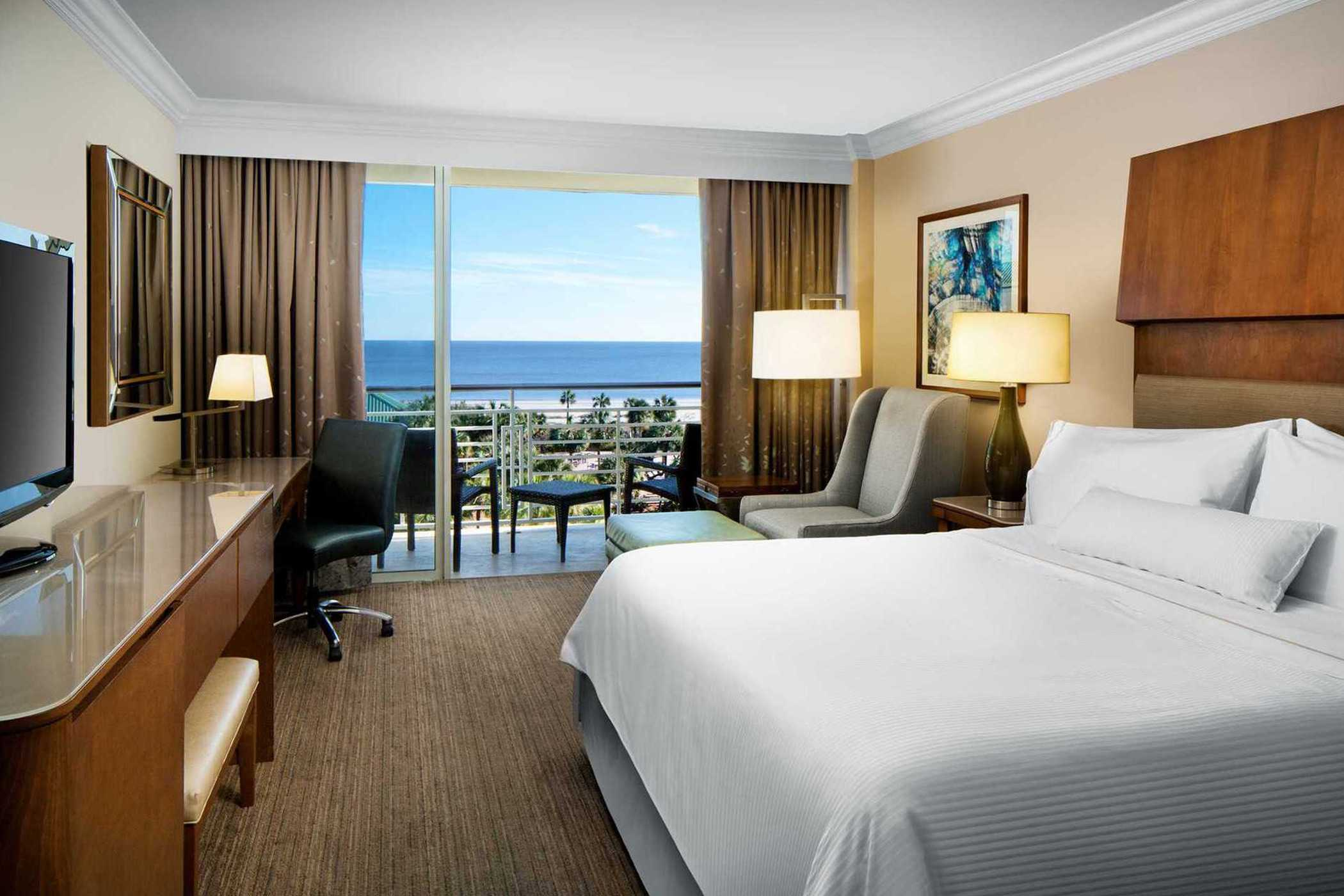a bright guest room with a large bed and a view of the ocean