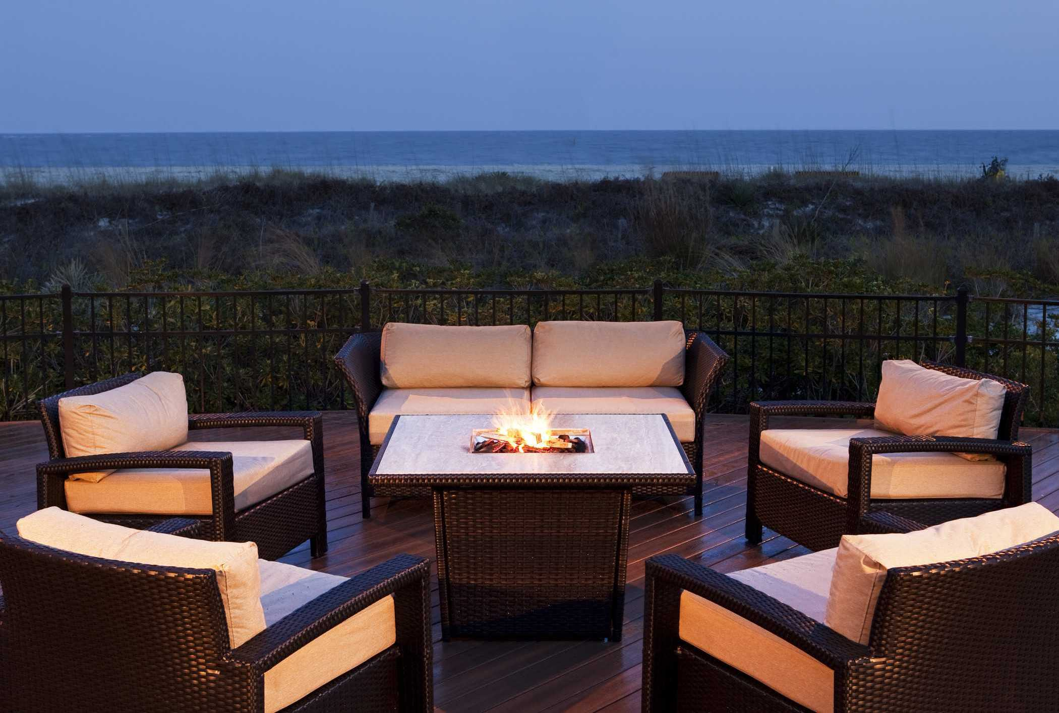 a bon fire on a patio next to the beach at dusk surrounded by chairs