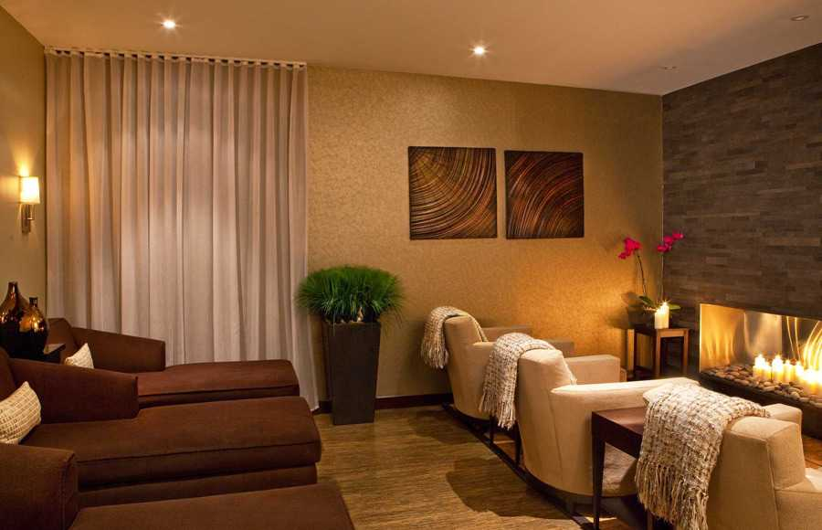 the spa relax room with lounge chairs and three armchairs in front of a fireplace