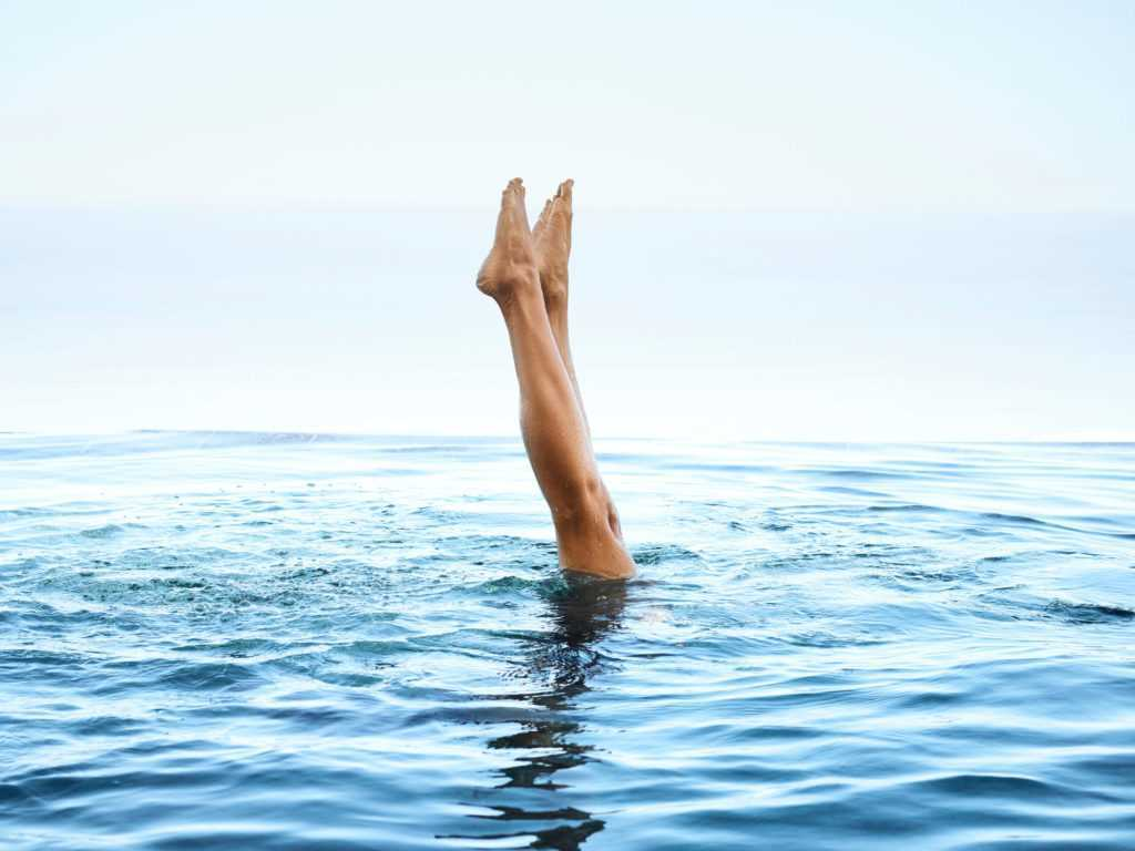 A swimmer with her legs sticking upright out of the blue water