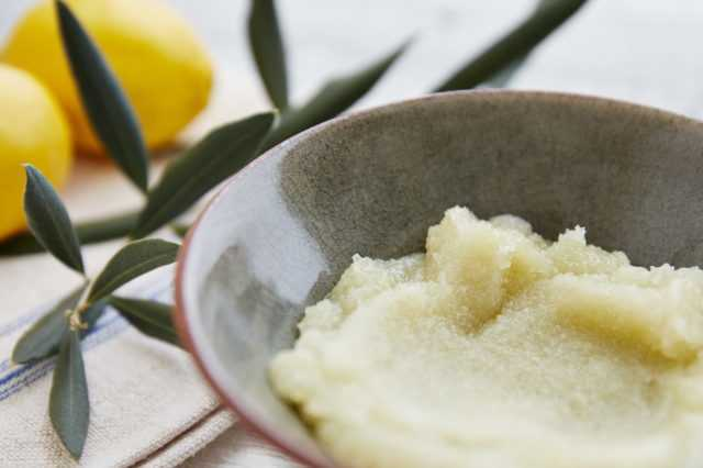 A bowl of body scrub neatly placed aside lemons