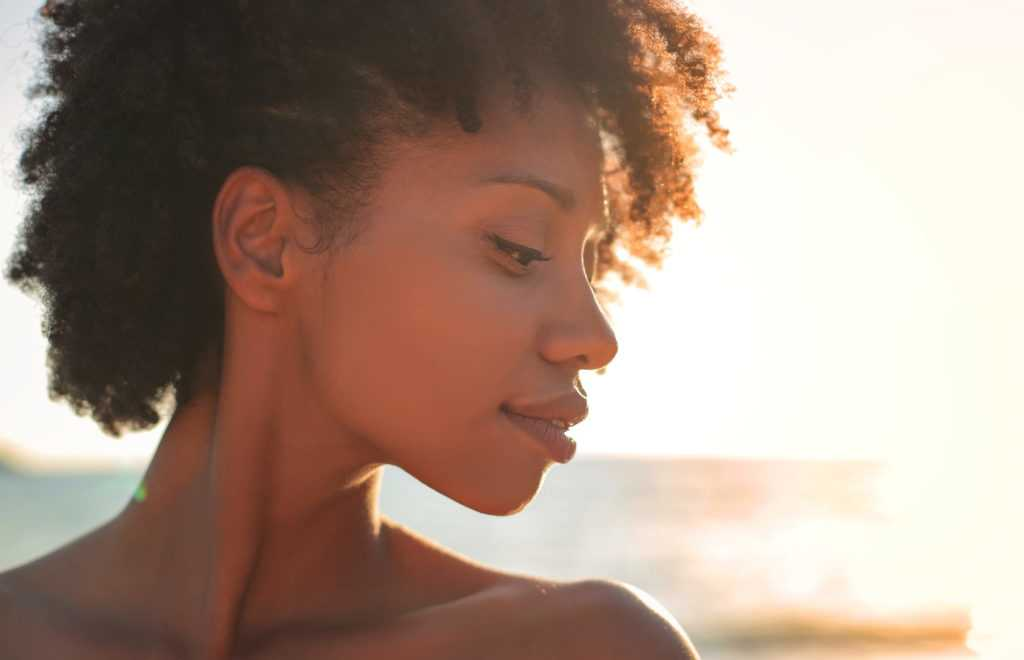 A fresh faced african american woman blissfully happy on a beach