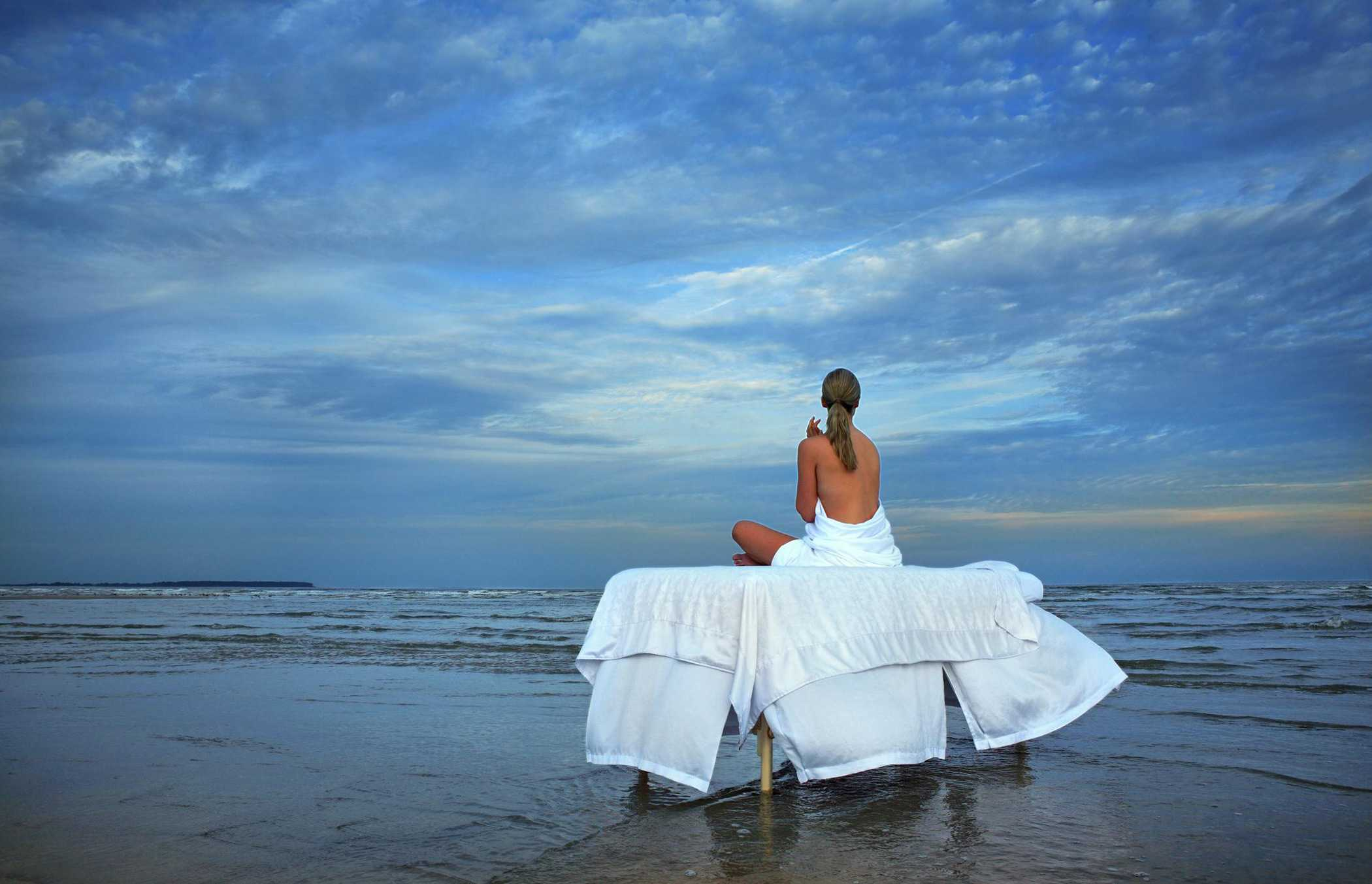A woman sitting on a massage table overlooking the beach at dusk
