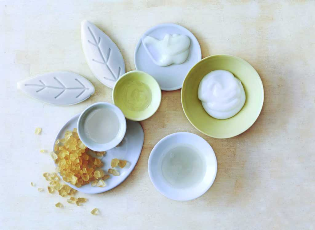 An arrangement of various bowls and plates holding spa scrubs and creams