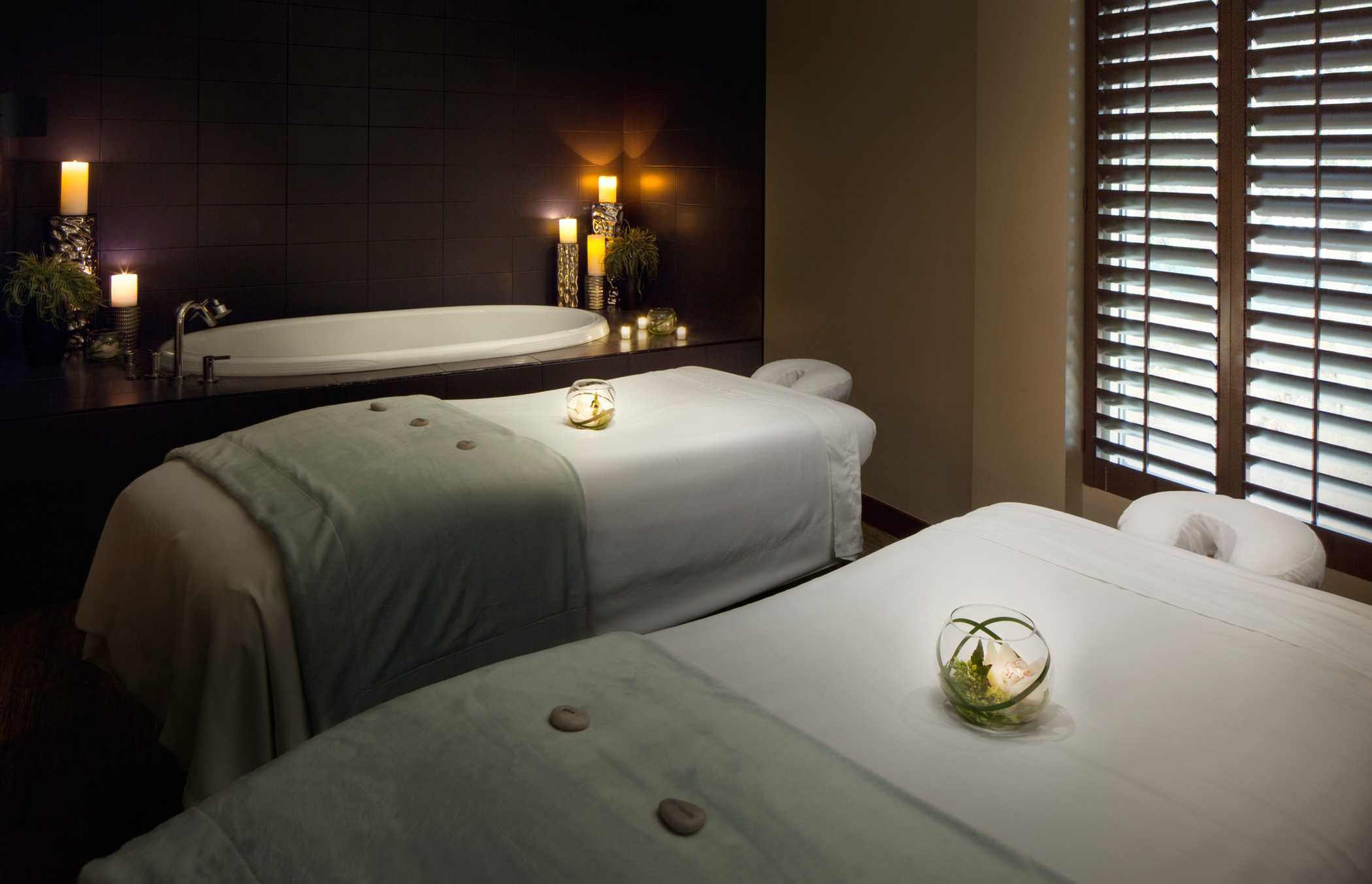A candlelit room with two prepped massage tables