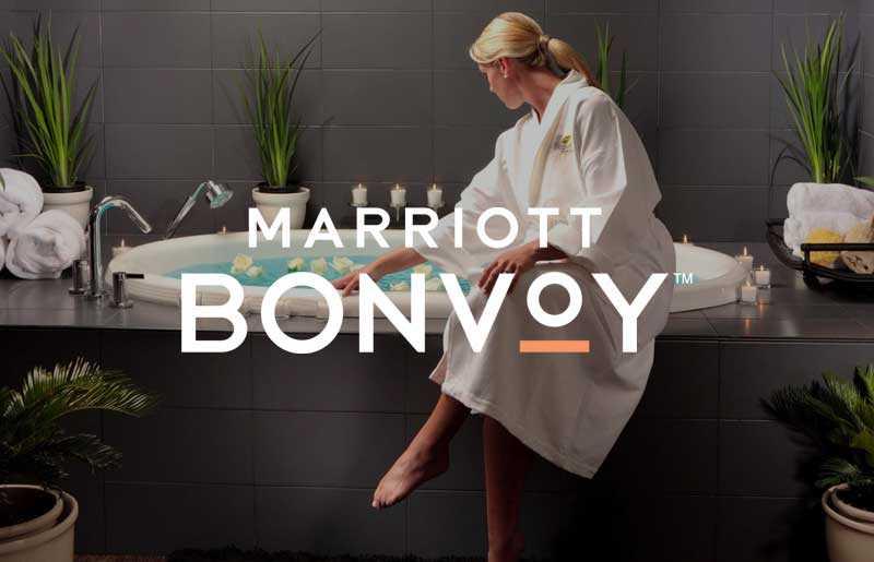woman in white robe sitting on edge of bathtub with marriott bonvoy logo on top