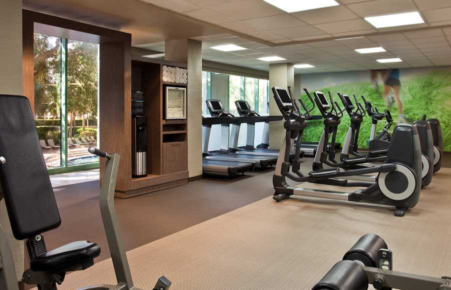 A fitness room full of gym equipment and large windows