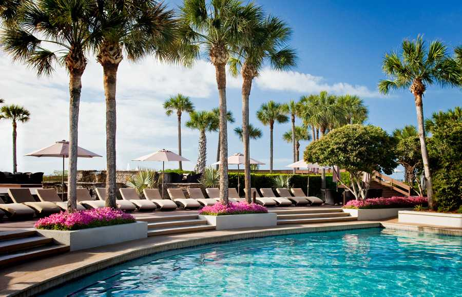 A pool with lounge chairs and palm trees surrounding the pool deck
