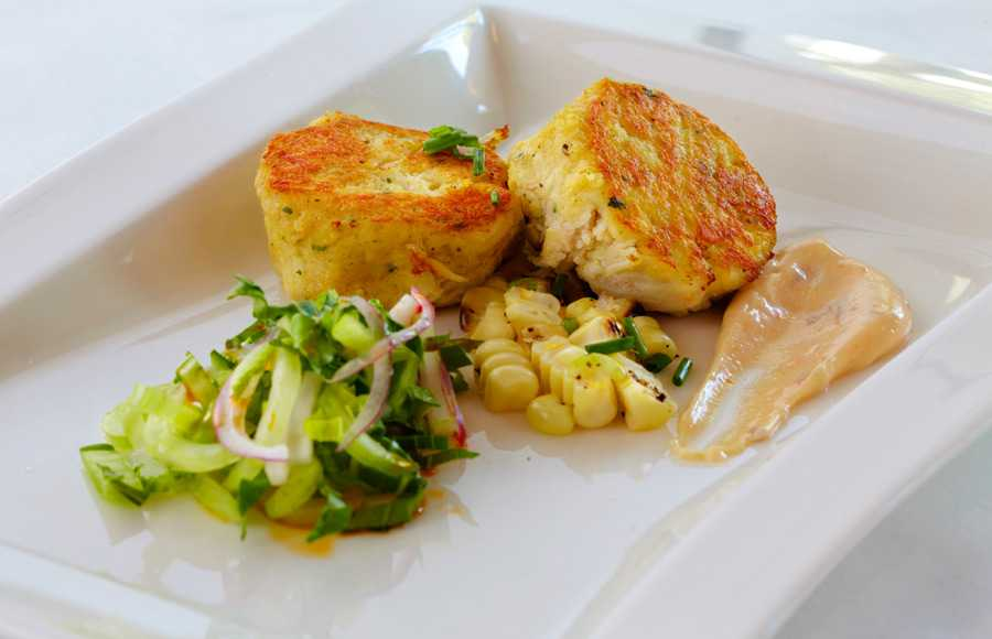 A delicious food shot of two crab cakes neatly placed on a crisp white plate