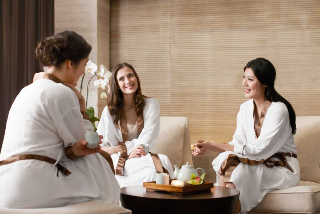 a group of three girls gathered around a table in their robes at a spa