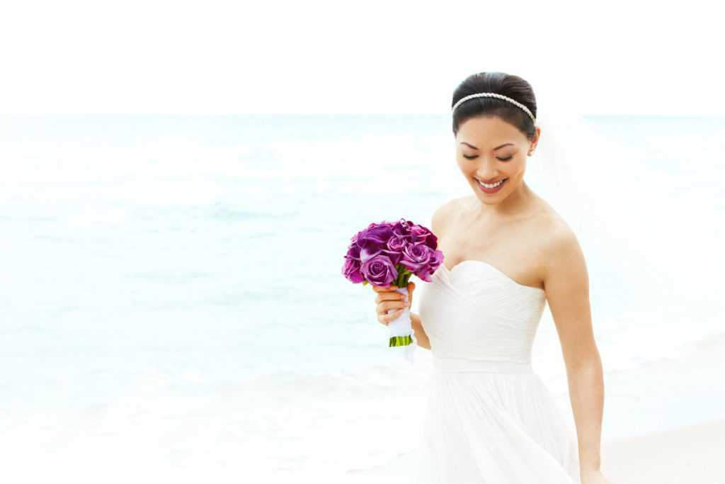 a bride holding a bouquet of flowers on a beach